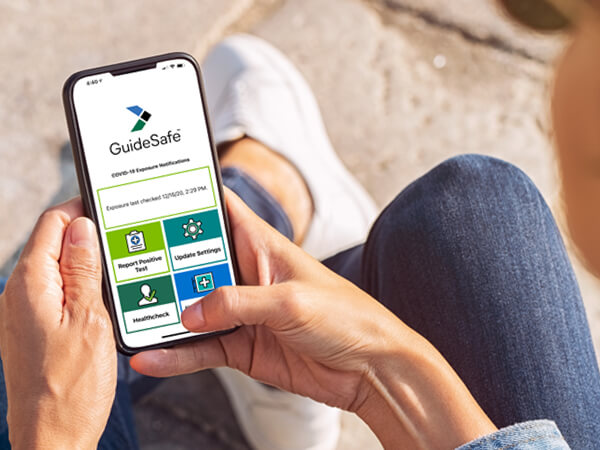 Hands holding a cell phone with the GuideSafe app open.