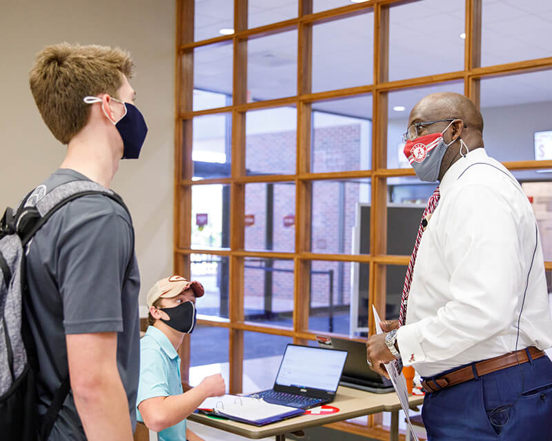 Two masked students speak to a black male professor wearing a UA facemask.