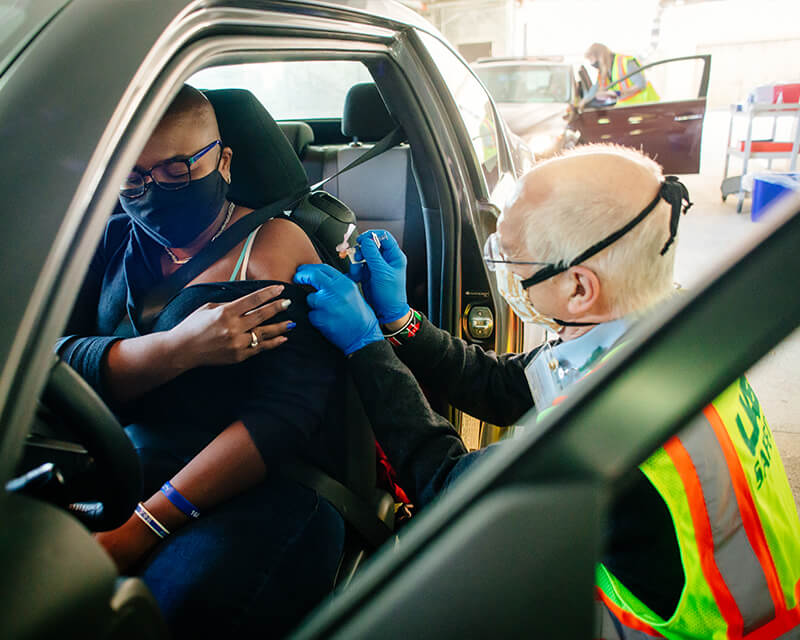 UAB Health System employee administers a flu shot to a patient at a drive-through flu shot clinic.