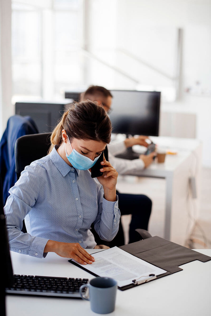 Employee at an office desk, wearing a mask, looking at a clipboard, & and talking on the phone.